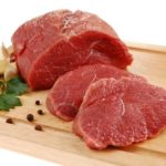 Raw beef on cutting board isolated on white background